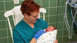 Mervi Lanu sitter i gungstolen och har nyfödda Ronja i famnen.