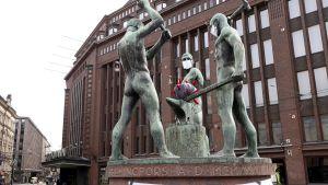Tre smeder-statyn bär andningsskydd. ''Hålls säker'' står det på statyns fot, och i mitten av statyn finns en boll som liknar coronaviruset.