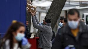 Flyktingar och flyktingarbetare tar emot sjukvårdsmaterial på det grekiska flyktinglägret Ritsona norr om Aten. Lägret har försatts i karantän på grund av coornasmitta på lägret.