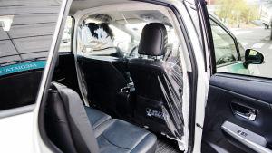 Kuvassa on taksi, johon on viritetty suojamuovi matkustajan ja kuljettajan väliin.