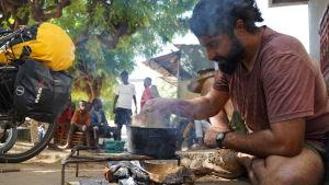 En man lagar mat ute över öppen eld