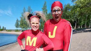 Karaktärerna Super-Malin och Super-Jontti som medverkar i serien Superhjälparna står på en strand och tittar mot kameran
