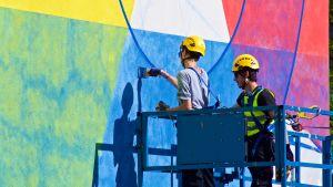 Två konstnärer målar en mural på en husvägg.