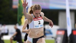 Lotta Kemppinen sträcker ut armen då hon korsar mållinjen.