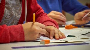 Elever skriver på papper med blyertspennor.