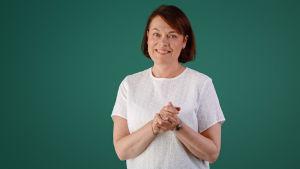 Martina Harms-Aalto står mot en grön bakgrund och småler mot kameran.
