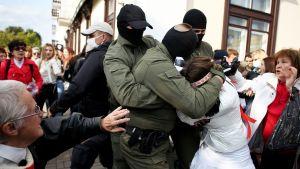 En polis håller fast en kvinna runt huvudet under en demonstration i Minsk den 12 september 2020.