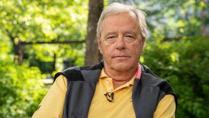 Man i gul skjorta sitter på en bakgård i Helsingfors. Bakom honom gröna bruskar.