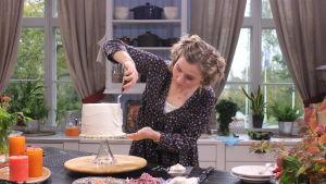 En kvinna täcker morotskakan med marängsmörkrämen