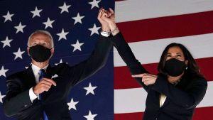 Kamala Harris står bredvid Joe Biden och håller upp hans hand.