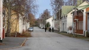 Tre kvinnor går på en tom gata. På vardera sidor syns gamla trähus.