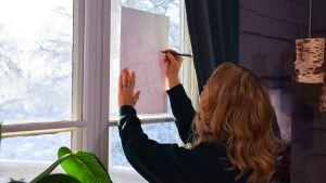 En kvinna som står med ryggen mot kameran och håller ett vitt papper mot ett fönster för att kunna teckna av ett mönster med hjälp av ljuset utifrån.