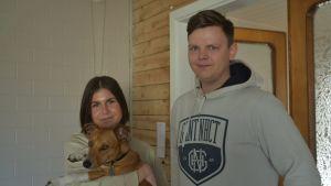 Ett ungt par med hund i famnen