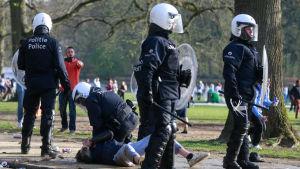 Polis i kravallutrustning, en polis håller en person på marken. Poliserna försöker skingra besökare på en fejkfestival i Bryssel.