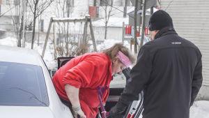 Anita Andersson får hjälp med att stiga ur taxin av chauffören Marko.