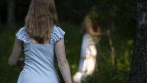 Kaksi tyttöä kulkee hämärässä kesäistä polkua lehdossa.