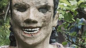 Staty föreställande kvinna med löständer och ögon av glas.