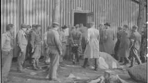 Människor utanför ett hus i det tyska fånglägret på Tulludden i Hangö