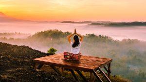 Kvinna mediterar i solnedgång.