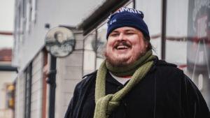 Stor man i svart kappa, grön halsduk och blå mössa står på vintrig gata och skrattar.