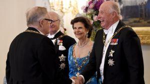 Glada miner när kung Harald skakar hand med president Martti Ahtisaari på Presidentens slott den 1 juni 2017.