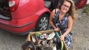 Ida Haapamäki med en låda skor som hon ska göra sig av med.