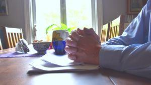 En mans knäppta händer vilar på ett bord.