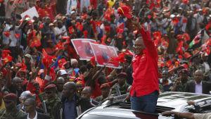 Kenyas president Uhuru Kenyatta vinkar till sina anhängare från en limousine.
