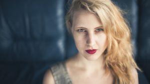 Kirjailija Anu Kaaja tuijottaa tiukasti kameraan