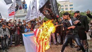 Palestinska demonstranter bränner amerikanska och israeliska flaggor i Gaza City på onsdagen den 6 december.