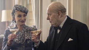 Clemmie (Kristin Scott Thomas) skålar med sin man Winston Churchill (Gary Oldman).