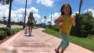 Moonee (Brooklynn Prince) springer, hennes mamma syns i bakgrunden.