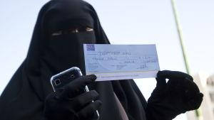 En kvinna i niqab håller upp en böteslapp som hon fått på grund av sitt klädesplagg i Frankrike.