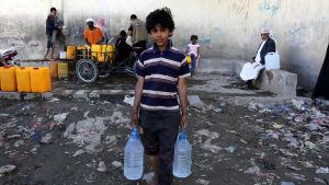 En pojke i Jemens huvudstad San'a håller två dunkar med vatten. Bristen på rent vatten är ett stort problem och har förvärrat koleraepidemin som härjar i landet.