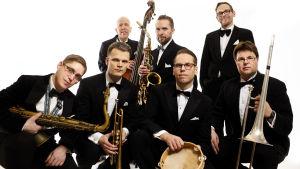 En frack-klädd manlig jazz-orkester med diverse blåsinstrument och cello står och sitter på huk med blicken rakt mot kameran. Vit bakgrund.