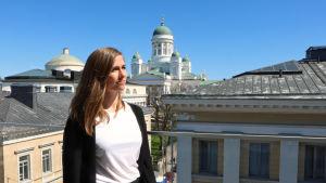 Janina Fagerlund, som jobbar på Reaktor, står på en balkong med Helsinfors domkyrka i bakgrunden