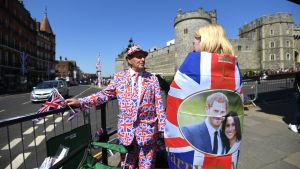 En man i kostym prydd med Storbritanniens flagga och en kvinna iklädd Storbritanniens flagga står framför Windsor slott.
