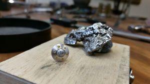 Gibeon meteoriitin kappale ja meteoriitista valmistettu korvakoru.