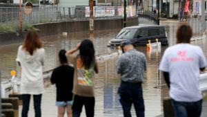 En grupp människor står och tittar på en översvämmad väg i Higohiroshima.