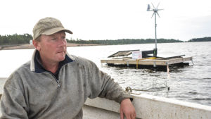 Fiskare Miakel Lindholm i båten. I bakgrunden syns sälskrämman.