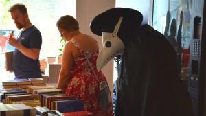 En person utklädd under Finncon tittar på böcker.