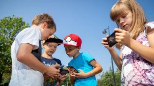 Tulevia ekaluokkalaisia ja koulunsa aloittaneita lapsia katsemassa kännyköitään, Leikkipuisto Soihtu, Paloheinä, Helsinki, 31.7.2018.