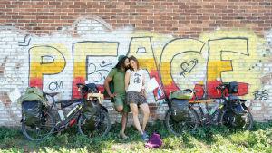 """En man och en kvinna står framför en grafittimålning som föreställer ordet """"peace"""". Bredvid sig har de sina cyklar som är fullpackade med väskor."""