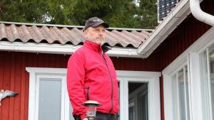En medelålders man i röd jacka och med keps på huvudet står vid ett terrassräcke vid en röd sommarstuga.