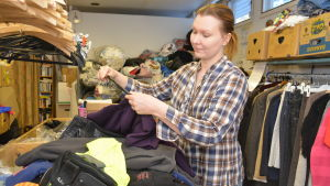 Laura Pihlaja sorterar återvunna plagg på Emmaus-Westervik.