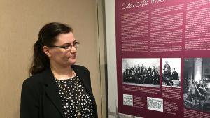 Sanna Linjama-Mannermaa står och tittar på utställningsplanscherna med svartvita bilder.