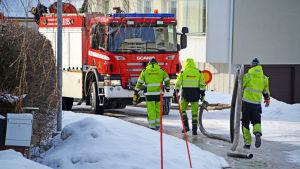 Män bär på rör och går mot brandbil