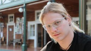 En ung man med långt ljust hår och glasögon sitter vid ett bord.