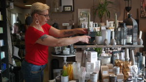 Terhi Pilke ordnar bland ljus i en hylla i sin butik Amalias hem