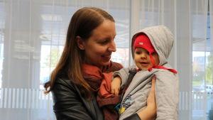 Linda Grönqvist står med sitt barn i famnen och ler mot barnet. Barnet skrattar.